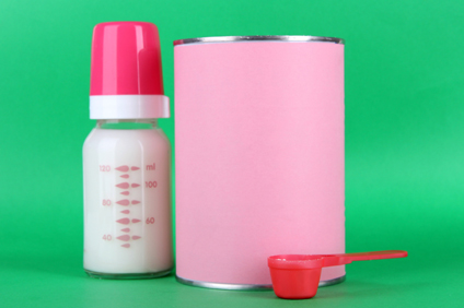 Powdered milk with baby bottle of milk on green background