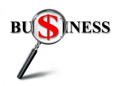 business red word and dollar on magnifying glass