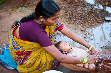 Indian woman washing her baby