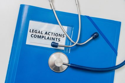 Legal Actions and Complaints in blue folder. Medical failure concept.