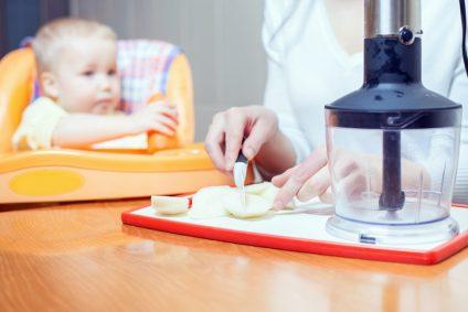 Mother cooking in blender pure for baby