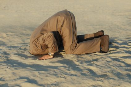 Businessman with head stuck in sand at the beach