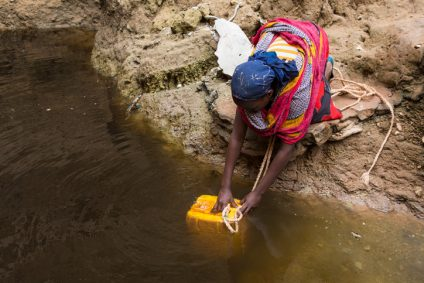 Ethiopian woman takes water from a well