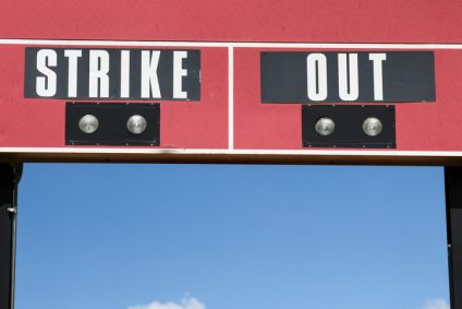 "Portion of a red baseball scoreboard that says ""Strike Out"""