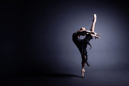 Young ballerina in a black suit is dancing in dark