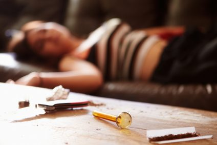 Woman Slumped On Sofa With Drug Paraphernalia In Foreground