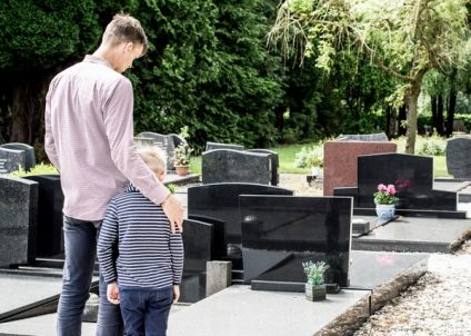 father with kid visiting grave