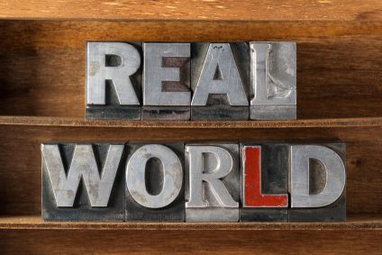 48455727 - real world phrase made from metallic letterpress type on wooden tray