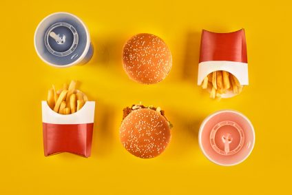 Fast food and unhealthy eating concept - close up of fast food snacks and cold drink on yellow background