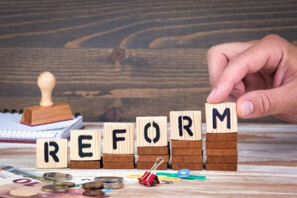 Reform concept. Wooden letters on the office desk, informative and communication background