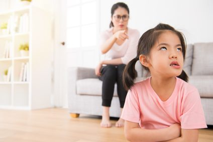 asian mother sitting on the sofa angry pointing