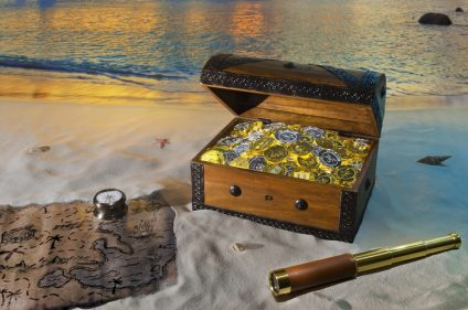 Treasure chest with gold coins on a beach