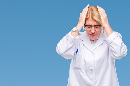 Middle age blonde therapist woman wearing white coat over isolated background suffering from headache desperate and stressed because pain and migraine. Hands on head.