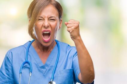 Middle age senior nurse doctor woman over isolated background angry and mad raising fist frustrated and furious while shouting with anger. Rage and aggressive concept.