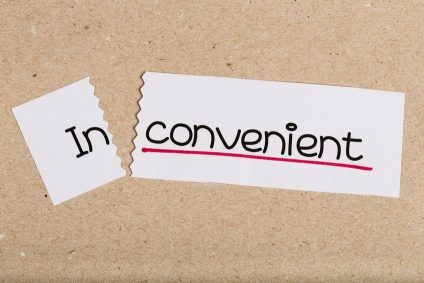 Two pieces of white paper with the word inconvenient turned into convenient
