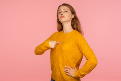 This is me! Portrait of attractive haughty ginger girl in sweater pointing at herself and looking at camera with arrogance